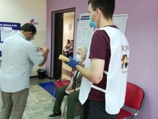 Волонтер измеряет температуру. Предлагает поучаствовать в викторине